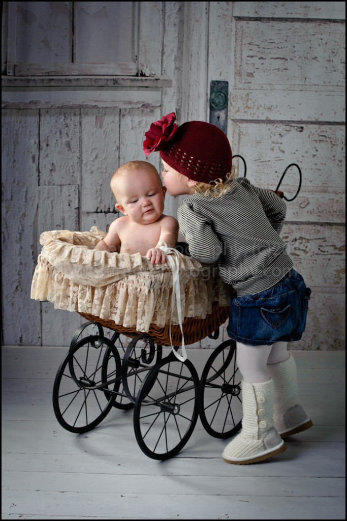 Two Year Old kissing baby sister portrait at St Charles Children's Photographer studio
