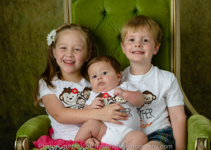 Baby with siblings in the studio by St Charles Photographer