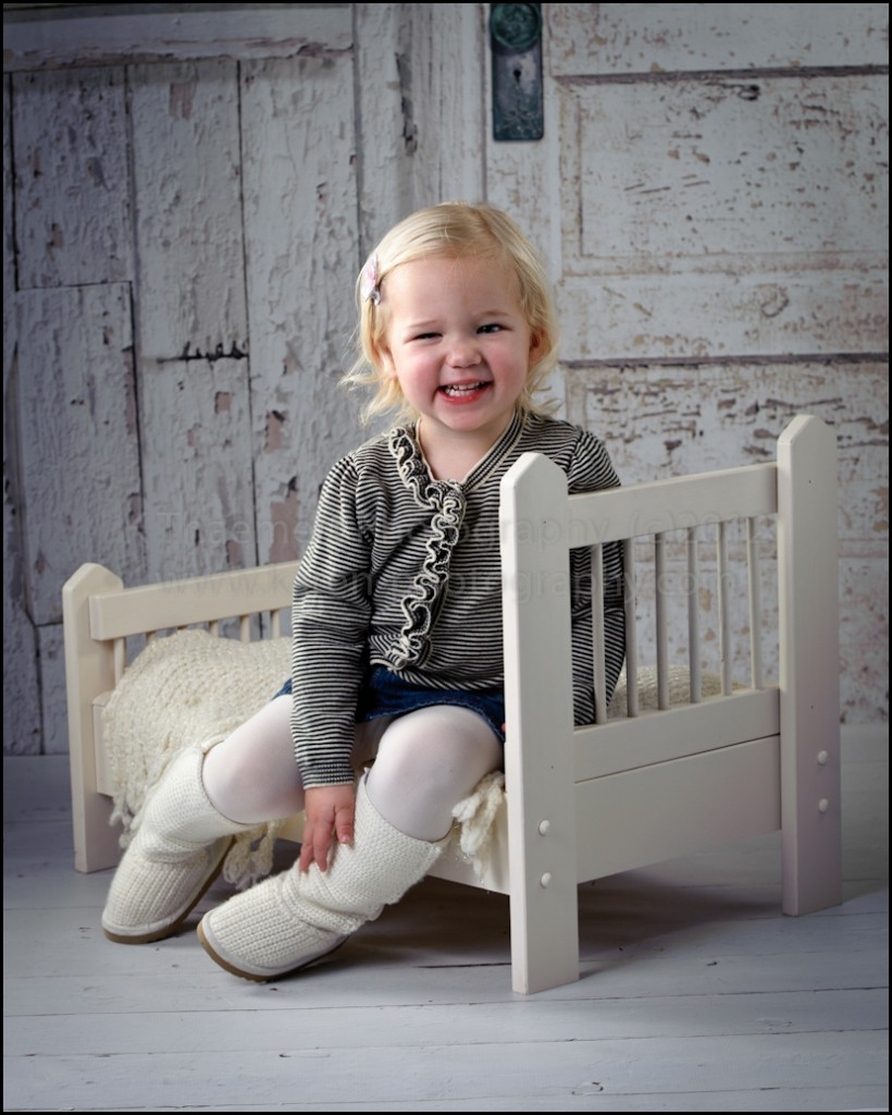 Two Year Old sitting on baby bed at St Charles Children's Photographer studio