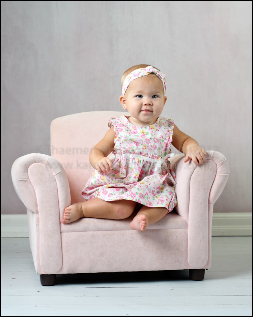 9 month girl in plush pink chair by St Charles Baby Photographer