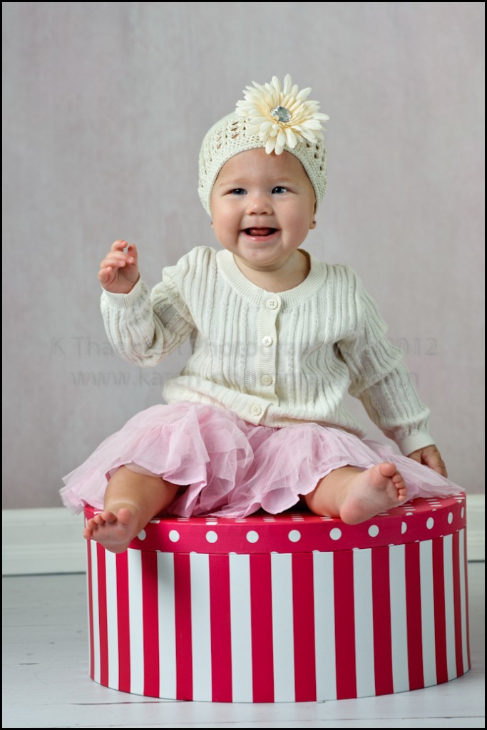 Smiling baby girl on hat box by St Charles Baby Photographer