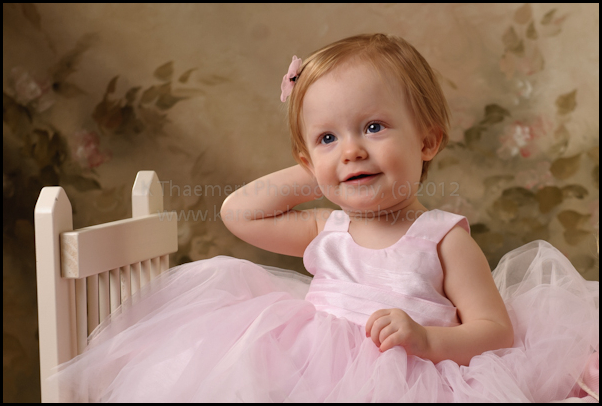 St Charles Child Photographer portraits of baby girl in pink dress on little bed