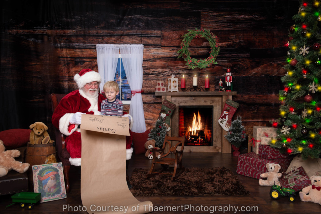Little Boy peeking at Santa's Naughty Nice list at his Santa Experience Portrait Session